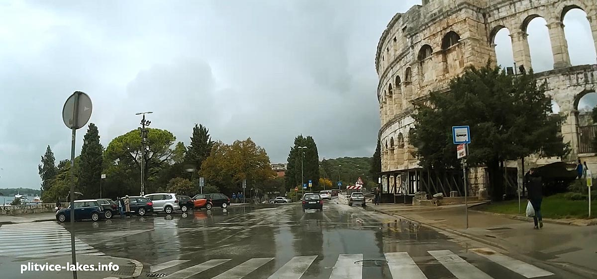 Driving in Pula passing by amphitheatre